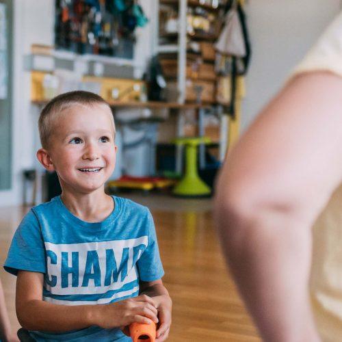Ein Bub hält ein Spielzeug in der Hand und sieht dabei lachend Angelika Reichartzeder an.