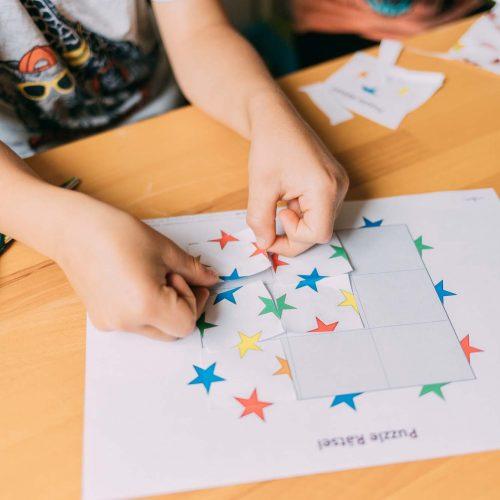 Kinder schneiden Papiere zusammen und kleben die Stücke auf ein großes Papier um so ein Puzzle zu lösen.